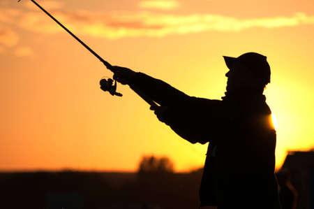 hengelsport: Fisherman silhouet bij zonsondergang