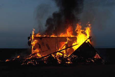 Burning old abandoned house at dusk photo