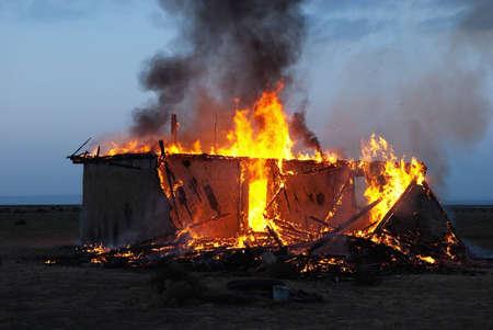 incendio casa: Burning vieja casa abandonada en la oscuridad