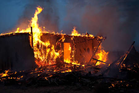 damages: Burning old abandoned house at dusk