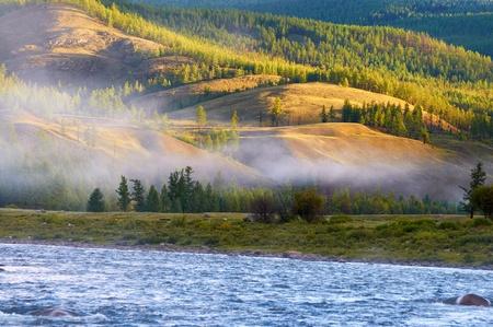 Morning fog on river Shishged in northern Mongolia Фото со стока