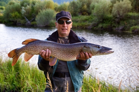 Fisherman with pike fish on the shore of river Uur in northern Mongolia Banco de Imagens
