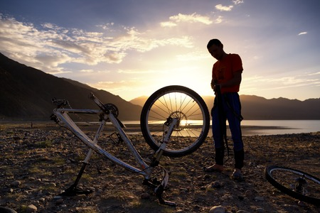 ALMATY, KAZAKSTAN - MAY 02, 2014: Silhouette of an athlete, who is preparing bike for the next day competition at Adventure mountain bike cross-country marathon in mountains Jeyran Trophy 2014