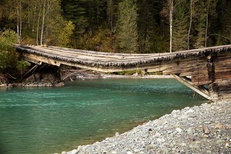 Gebroken houten brug over de rivier Belaya Berel in het oosten van Kazachstan