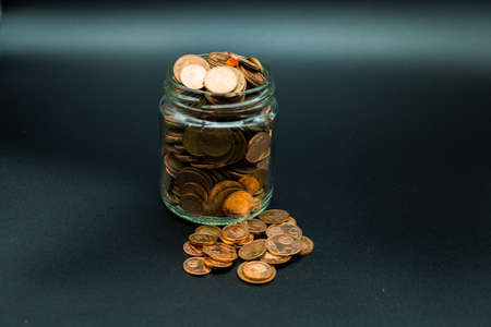glass jar with coins and bills on black background