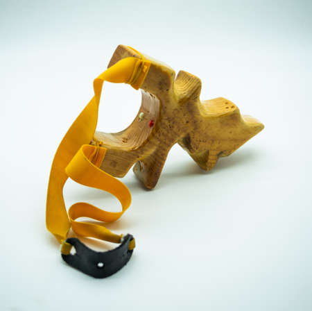 wooden slingshot with yellow rubber bands Foto de archivo