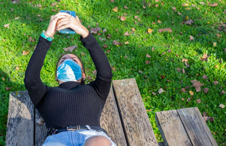 girl lying on a wooden bench, in the countryside, wearing a covid mask, speaks by video-conference with her friends Stock Photo