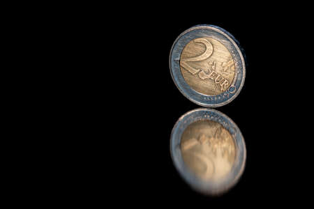 Euro coins isolated with pitch black background, reflecting in black metallic surface. Money on a very dark table.