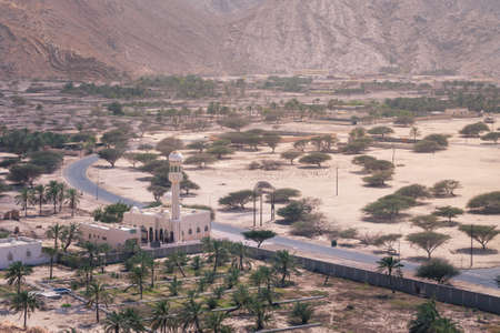 Small mosque in the rural area of Musandam province Suburbs of Bukha village, Oman. Palm trees in the desert under steep mountains.