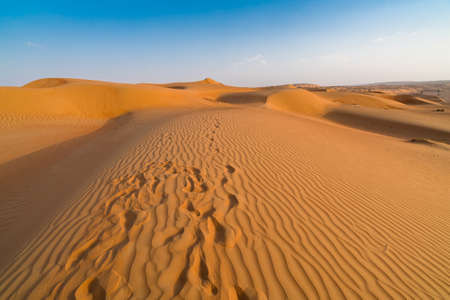 Sand dunes with footprints in them under the blue sky with soft haze on the distant horizon. Lae afternoon in the desert of Wahiba sands, Oman.