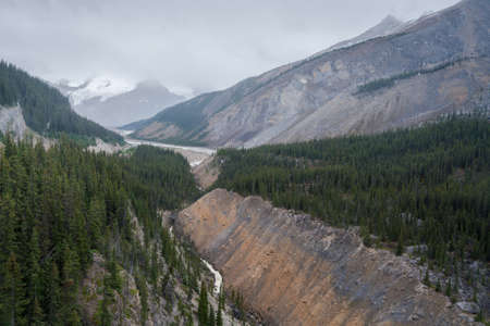 View from Columbia Icefield Skywalk into a valley in Canadian Rockies. Cold, cloudy, hazy day in the Icefield Parkway, Jasper National Park.