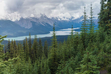 Clouds gathering above the mountain range in Canadian Rockies. Maligne lake in Jasper national park, Alberta, viewed from Bald Hills trail. Stock Photo