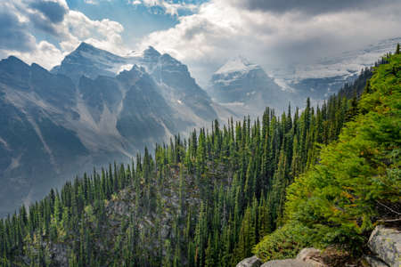 View of the trail to Big Beehive in Banff National Park, Alberta, Canada. Steep cliffs above alpine valley. Mountain range in summer haze. Mountain pines and dramatic clouds in the sky.