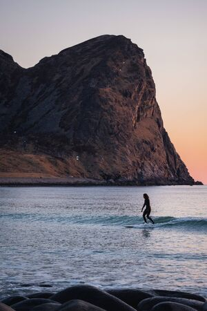 surfer on longboard. small waves during beautiful sunset. surfing behind arctic circle has advantage of midnight sun. Unstad is a famous beach in Lofoten Islands. iconic mountain in background Foto de archivo