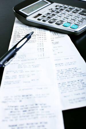 A calculator, a pen, bills, receipts on the black table