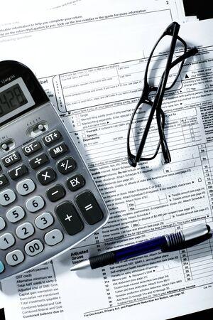 bookkeeper: Forma, una calculadora, una pluma en la tabla de impuestos