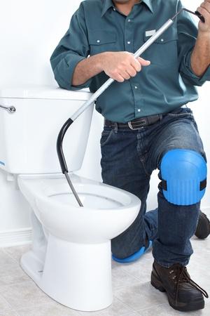Plumber fixing a flush toilet