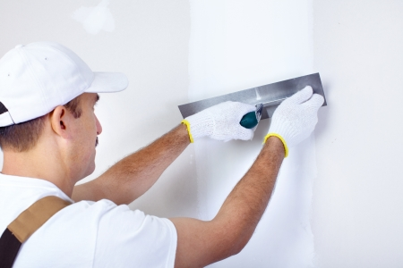 plastering: Mature contractor plasterer working indoors  Stock Photo