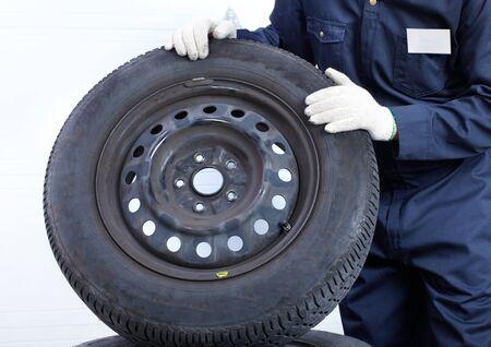 mechanic man holding an auto wheel  Stock Photo