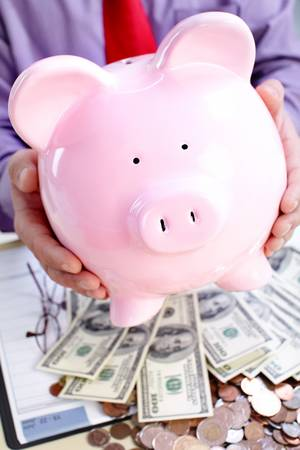 Businessman holding a pink pig bank