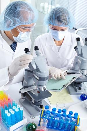 bata de laboratorio: Equipo de ciencia trabajar con microscopios en un laboratorio