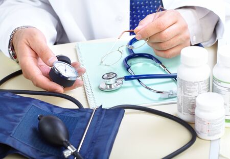 presure: Medical doctor holding a blood presure sphygmomanometer with stethoscope  Stock Photo