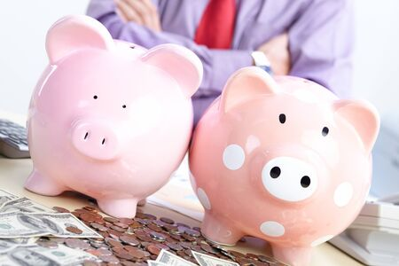 Businessman with money and a pink pig bank