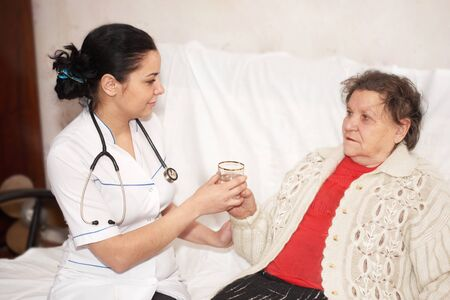 hospice: Senior woman is visited by her doctor. Medicine Stock Photo