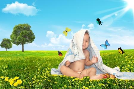 baby towel: Hermoso beb� mirando hacia fuera de debajo de una toalla sobre un fondo verde. Verano
