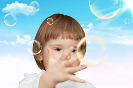The small girl plays with soap bubbles. Nature photo