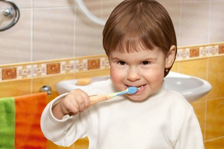 The small girl cleans teeth in a yellow bathroom