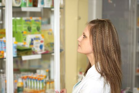 Medicine. Chemist woman standing in pharmacy drugstore. A female portrait Stock Photo - 13845459
