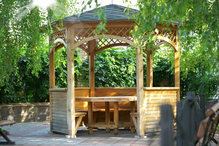 Wooden summerhouse is in a morning green park  photo