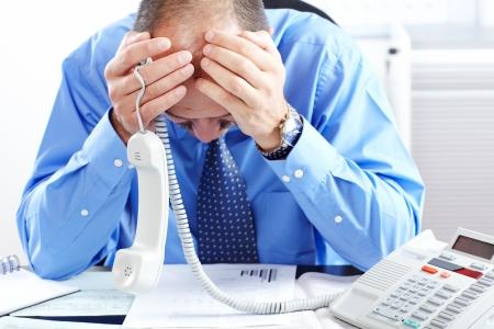 communication occupation: Uomo d'affari in una camicia blu con lo stress in ufficio Archivio Fotografico
