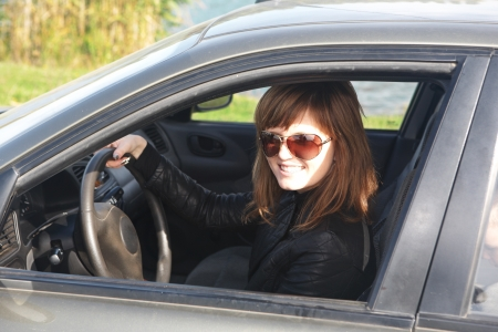 The beautiful  girl sits in the automobile photo
