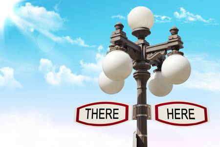 There and here. Direction sign and street lamp photo