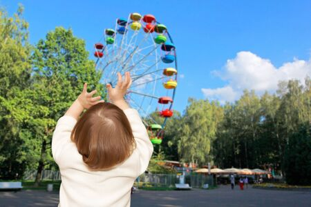 The small girl plays in park. The Ferris wheel photo