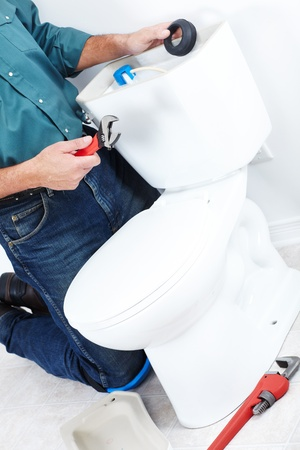 Plumber with a toilet plunger. The worker photo