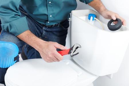 outils plomberie: Plombier avec un piston de toilette. Le travailleur Banque d'images