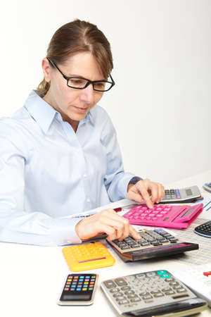Businesswoman in spectacles sits at office near calculators photo