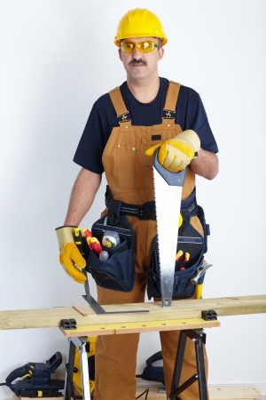 Contractor working with hack-saw and wooden board