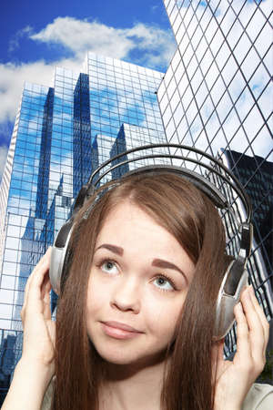 Girl listening to the music. The skyscrapers photo
