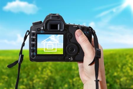 Woman photographing house with digital photographic camera photo