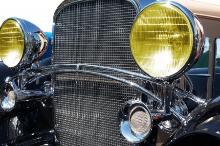 The retro car stands in a field. The headlight photo