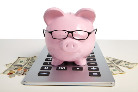 Pig bank on calculator on a white background photo