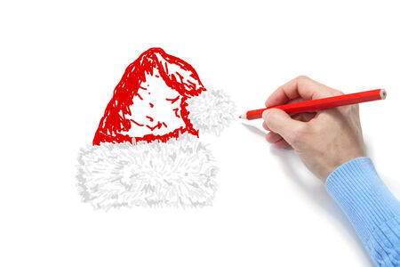 The hand draws a fur-cap on a white sheet of a paper photo