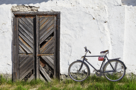 Old wooden door. A bicycle near house photo