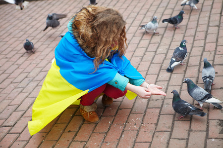 disillusionment: The girl with a flag feeds the pigeons on the square.