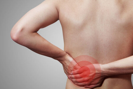 hand pain: Young male holding his back in pain Stock Photo