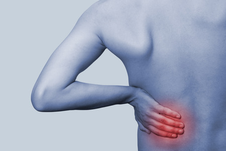 nephritis: Young male holding his back in pain. On a blue background